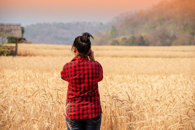 Красивая азиатская женщина наслаждаясь в полях ячменя