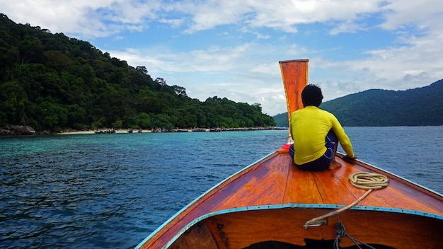 タイのリペ島で透き通った水、山、明るい青空とロングテールボート
