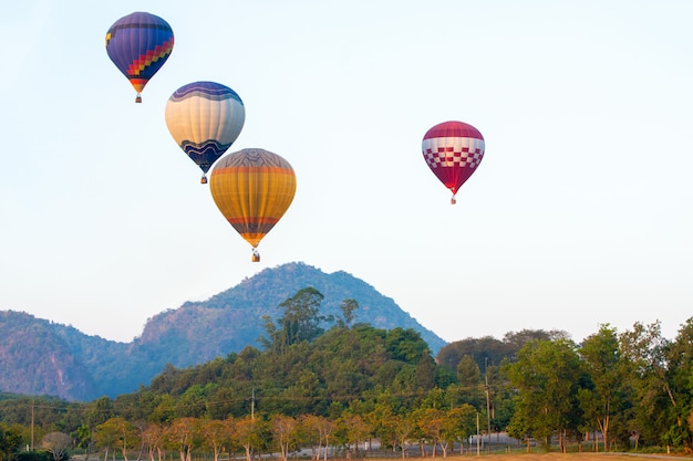 Красивый вид на воздушный шар на красочный закат над деревьями рядом с горами