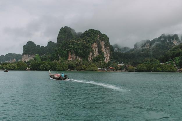 バックグラウンドでの風景とクラビ海のロングボート
