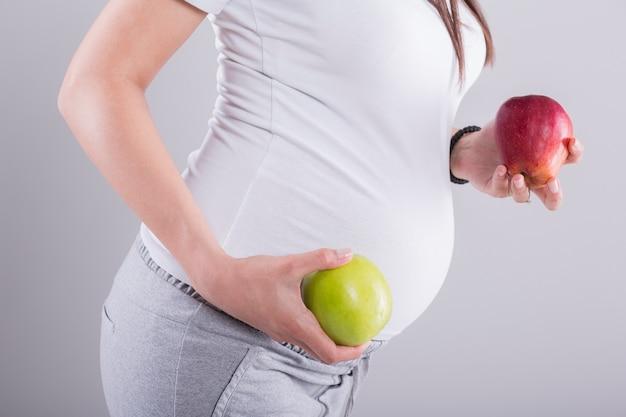 リンゴを持つ妊娠中の女性