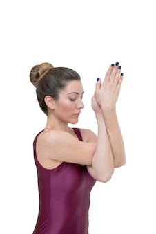 Женщина, практикующая йогу в позе гарудасана