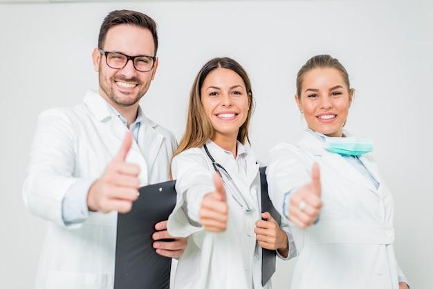 白い壁で親指で医師の親切なグループ
