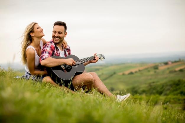 彼のガールフレンドと芝生に座ってギターを演奏する愛する男