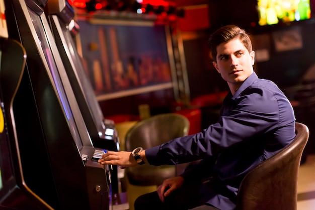 カジノのスロットマシンを持つハンサムな若い男