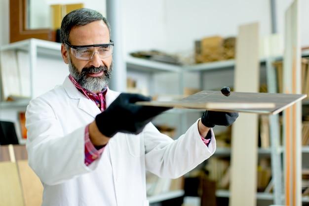 Красивый зрелый инженер, тестирующий цвета на деревянных образцах на мебельной фабрике