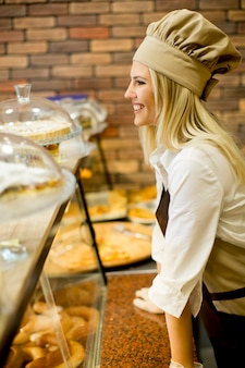 パン屋でパンを売っている若い女性