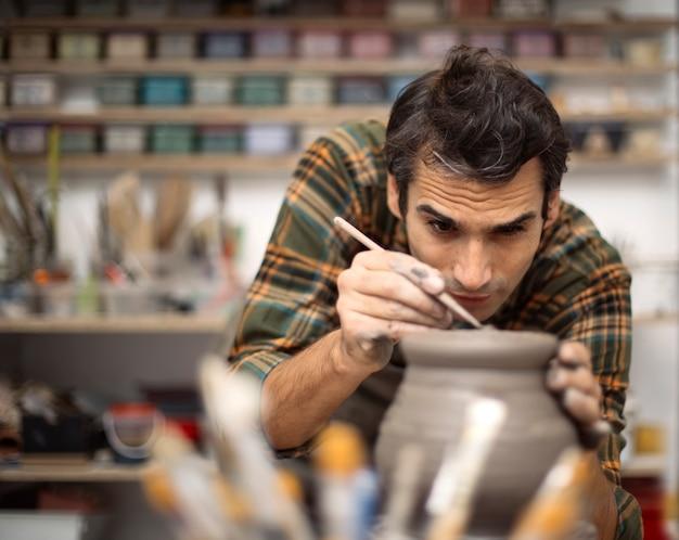ワークショップで若い男が陶器を作る