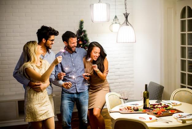 明るい女性と男性が輝きとワインで新年の夜を祝う