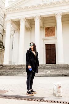 通りに犬と歩いている女性