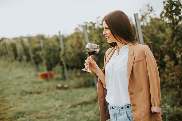 ぶどう園でワインのガラスを持つ女性