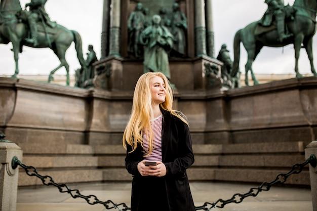 ウィーン、オーストリアの通りに携帯電話で若い女性
