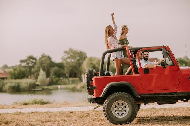 休暇でコンバーチブル車で楽しむ幸せな友達