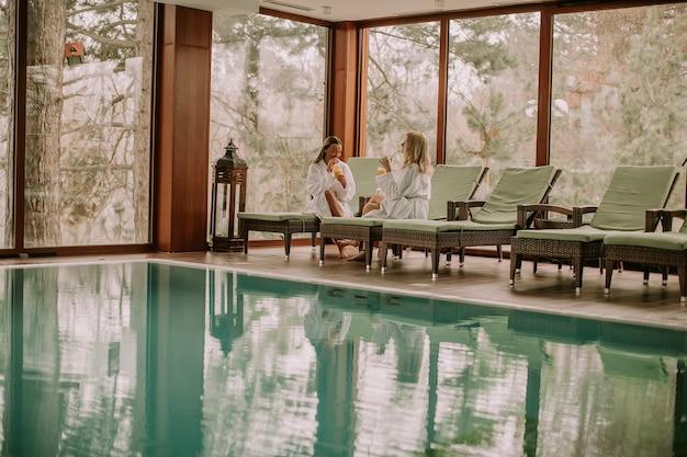 プールでデッキチェアでリラックスしている若い女性たち