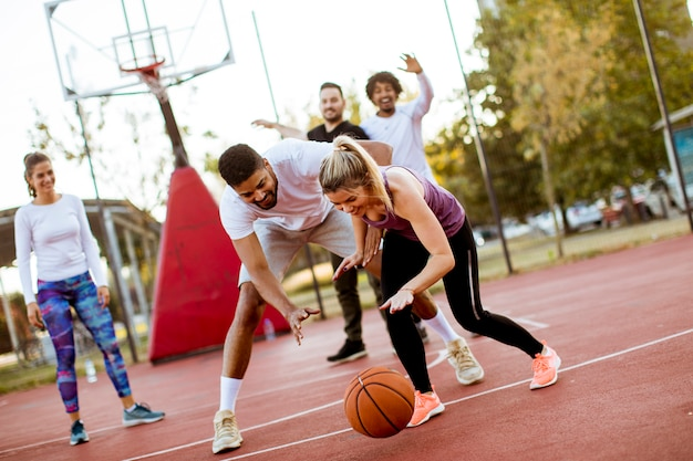 Группа многорасовых молодых людей, играющих в баскетбол на открытом воздухе