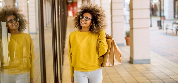 ショッピングの巻き毛を持つ若い黒人女性