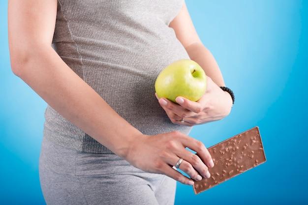リンゴとチョコレートの妊娠中の女性
