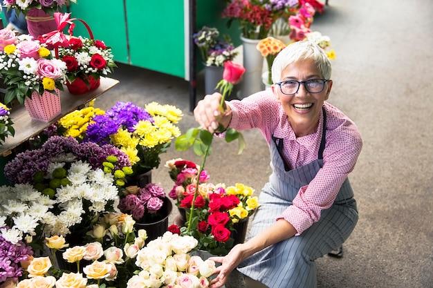 年配の女性が地元のフラワーマーケットに花を生ける
