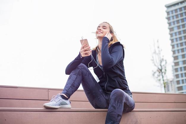 若いスポーティな女性休んでフィットし、トレーニング後の携帯電話で音楽を聴く