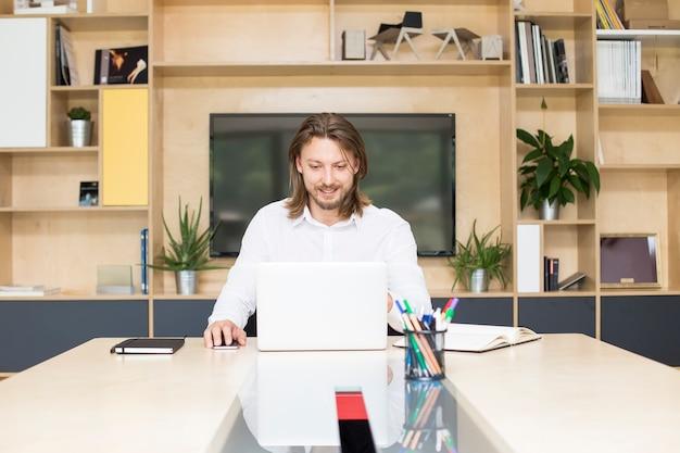 カジュアルな服装の青年実業家、オフィスの机に座っている間、ラップトップに取り組んで
