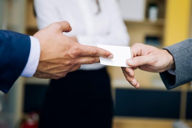 ビジネスカードを交換するビジネスマンのクローズアップ