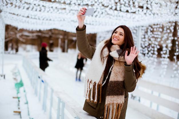 Молодая женщина в зимней одежде, принимая селфи на смартфон на открытом воздухе