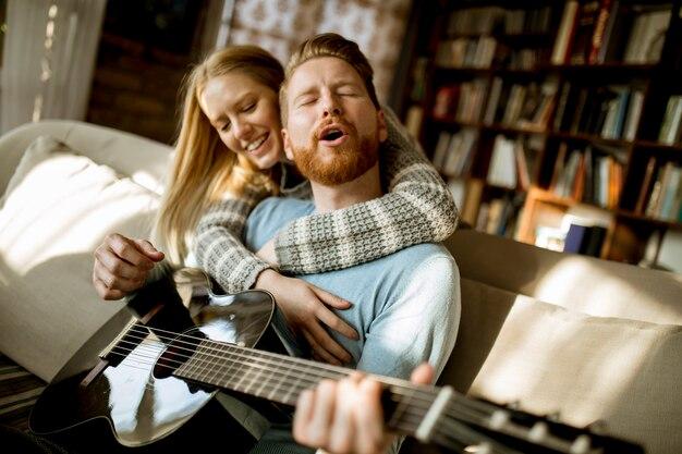 Мужчина играет на акустической гитаре на диване