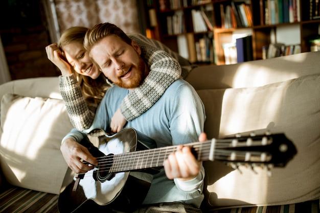 Человек играет на акустической гитаре на диване для своей молодой красивой женщины