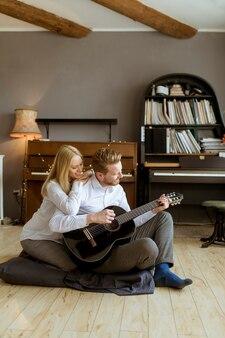 Мужчина играет на акустической гитаре для своей молодой красивой женщины