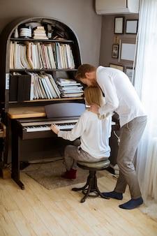 Любящая молодая пара играет на пианино