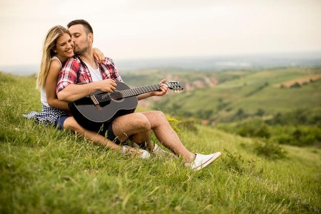 若い男が彼のガールフレンドと草の上に座っているとギターを弾く