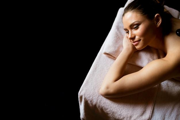 Молодая женщина с массажем горячими камнями