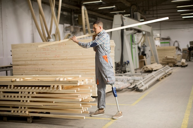 義足を持つ障害者の若者が家具工場で働いています。