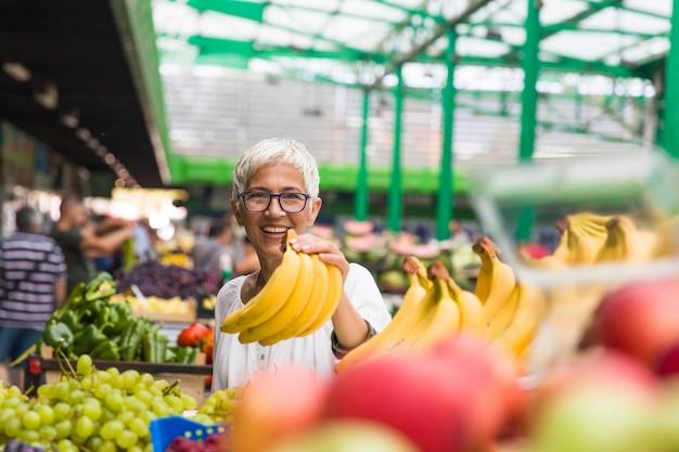 Портрет старшей женщины покупает бананы на рынке