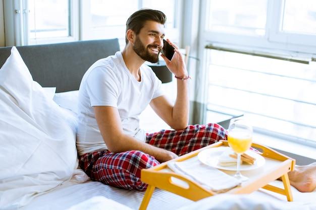 若い男がベッドで朝食をとり、携帯電話を使用して