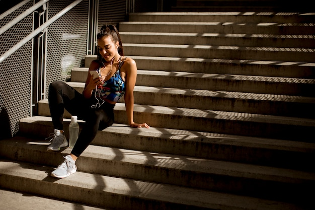 若い都市の環境で階段で屋外トレーニング後休んでスポーティな女性の休息と携帯電話で音楽を聴く