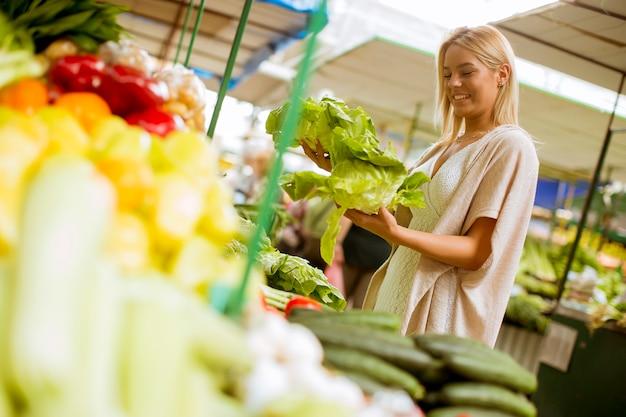 かわいい若い女性が市場で野菜を買う