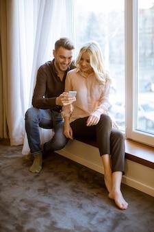 愛情のあるカップルは窓の近くに座って、アパートで無線インターネットを使用して、日中の光を楽しんで、携帯電話を使用
