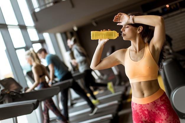 黄色のスポーツシャツの若い女性はジムで水を飲む