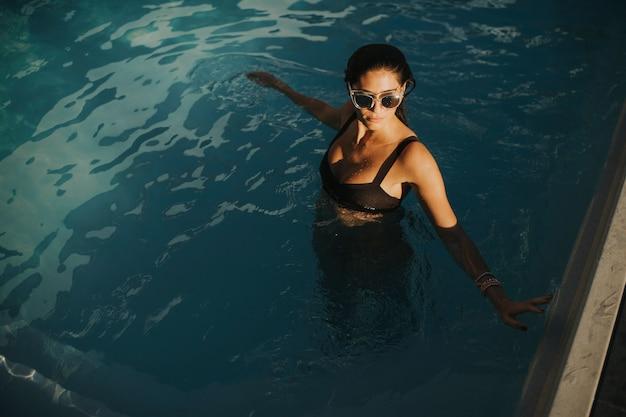 Милая молодая женщина в открытом бассейне