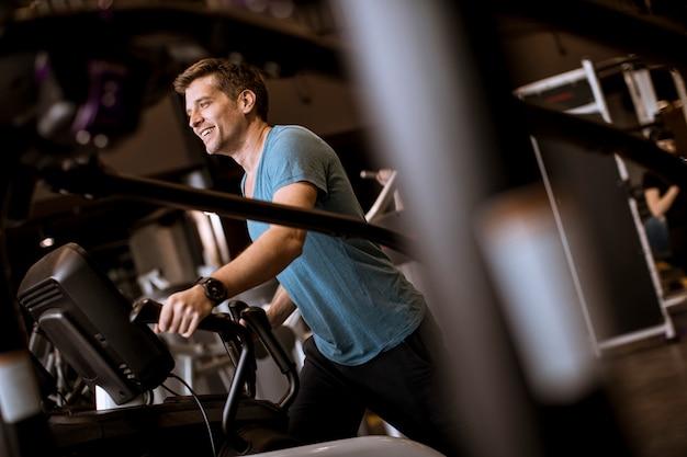 スポーツフィットネスジムクラブで楕円形のクロストレーナーの運動をしている人