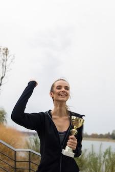 ゴールドトロフィーカップを保持している幸せなスポーティな若い女性