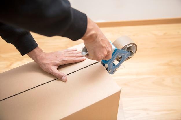 Руки человека с помощью диспенсера ленты, чтобы запечатать коробку