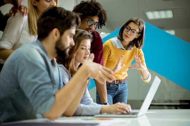 Группа молодых многонациональных деловых людей, работающих и общающихся вместе в креативном офисе