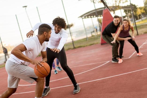 Группа многонациональных людей, играющих в баскетбол на корте