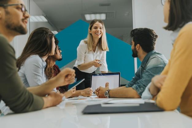 Довольно женского лидера команды, разговаривая с группой людей смешанной расы в офисе
