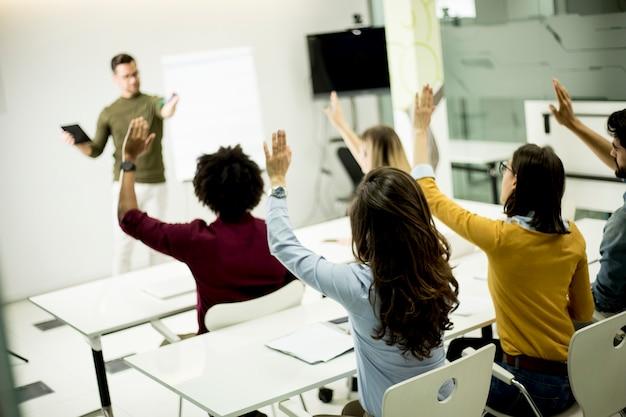 Студенты поднимают руки, чтобы ответить на вопрос во время семинара