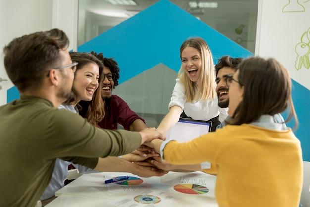 チームの人々がチームビルディングに従事しているテーブルの上に一緒に手をスタッキング