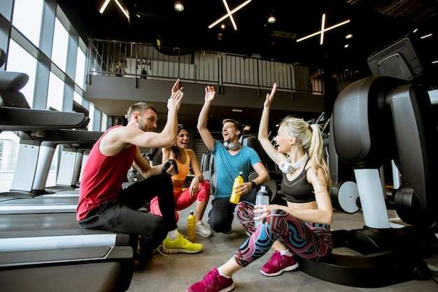 Друзья в спортивной одежде разговаривают и смеются вместе, сидя на полу в тренажерном зале после тренировки