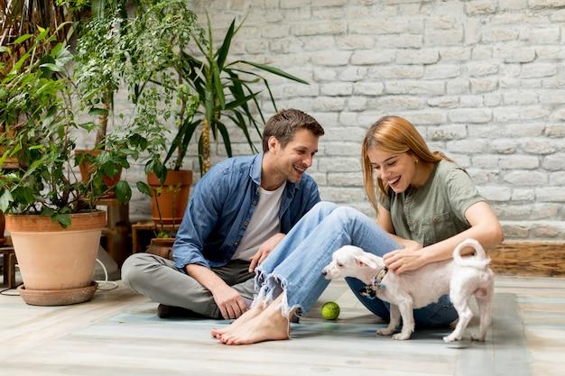 Молодая пара сидит на полу в загородном стиле и играет с собакой